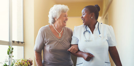 nurse assisting elder woman to walk