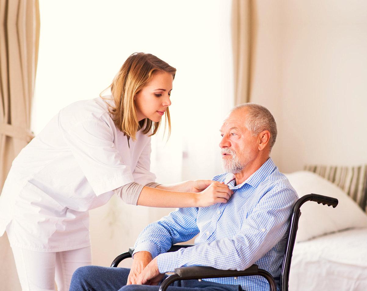 caregiver helping an elder man wear his polo
