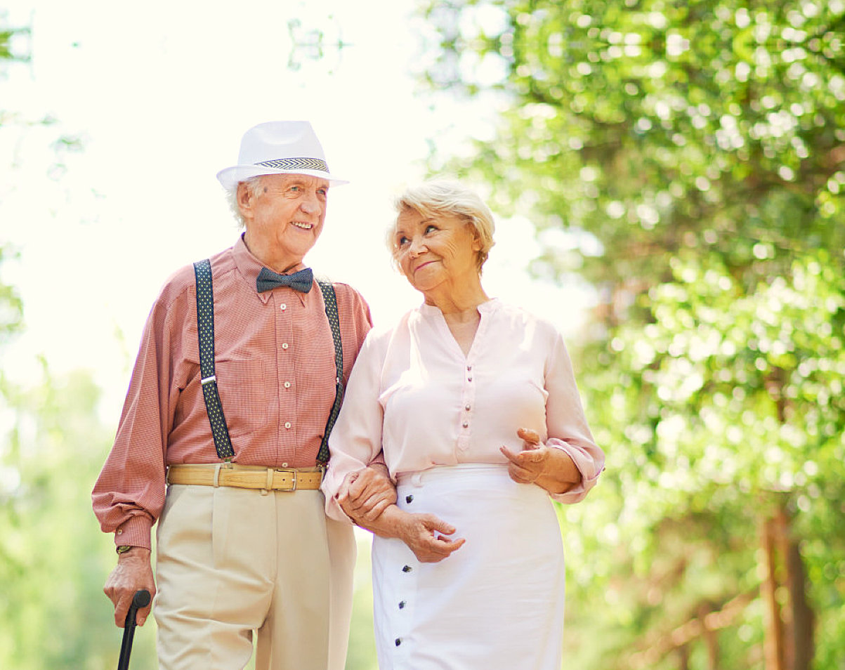 elderly couple walking while holding each other