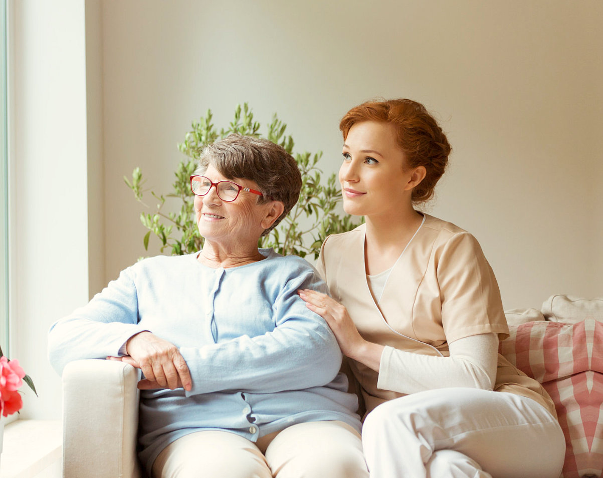 elder woman and caregiver looking out the window