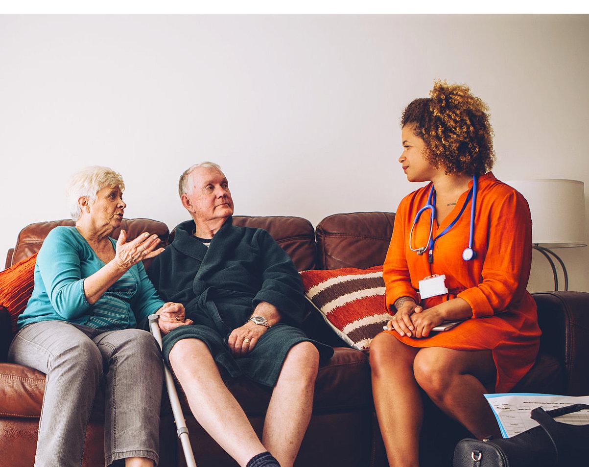 elderly couple talking to a nurse