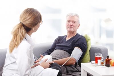 nurse taking the blood pressure of senior